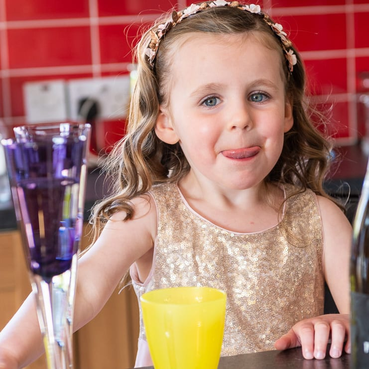 flower girl enjoys drink of juice before wedding