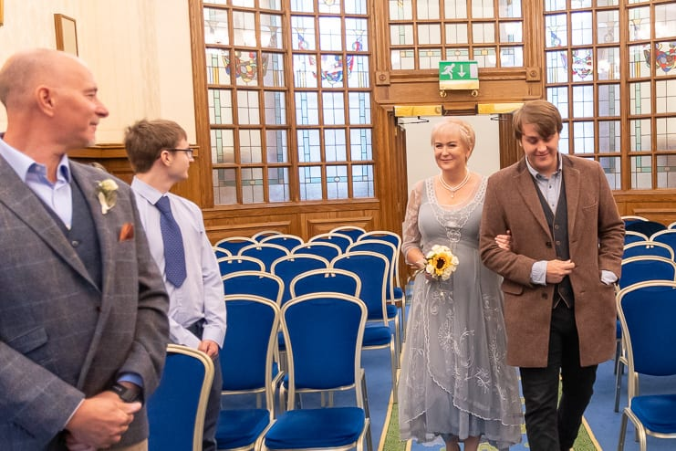 eldest son accompanies bride down the aisle as groom waits