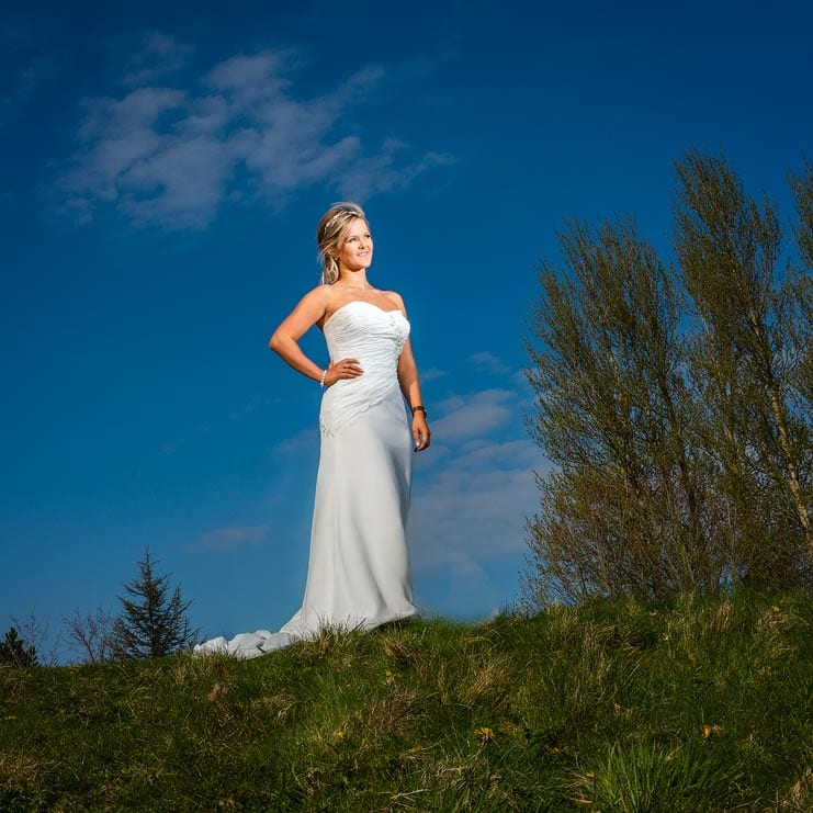 a bride on a hill top with a blue sky background