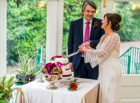 the bride and groom cutting the cake at this country house wedding