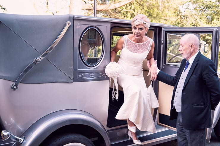 the bride alighting from her vintage wedding car