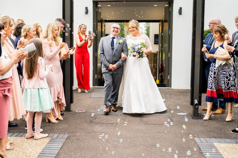bride and groom as guests make bubbles