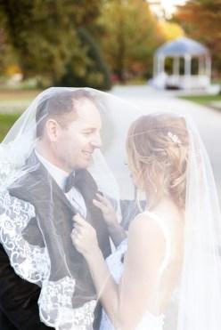 groom smiling under the bride veil