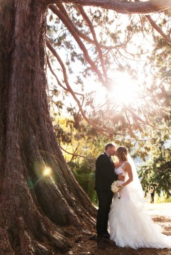 portrait of bride and groom kissing with a lens flare
