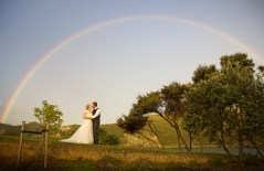 auckland wedding photographer's photo of the bride and groom kissing under a rainbow by Oke Bay