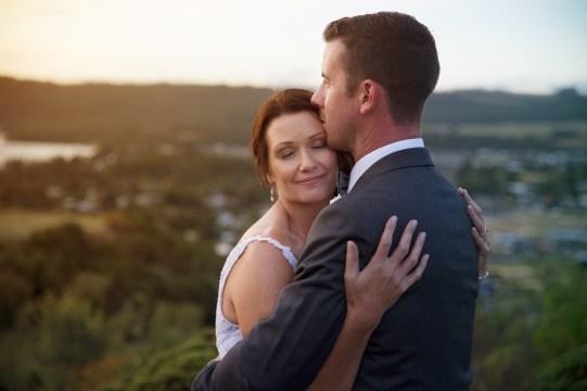 auckland wedding bride hugging groom sunset