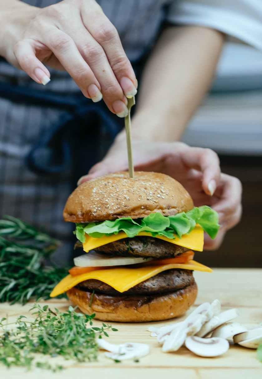 crop woman serving delicious burger