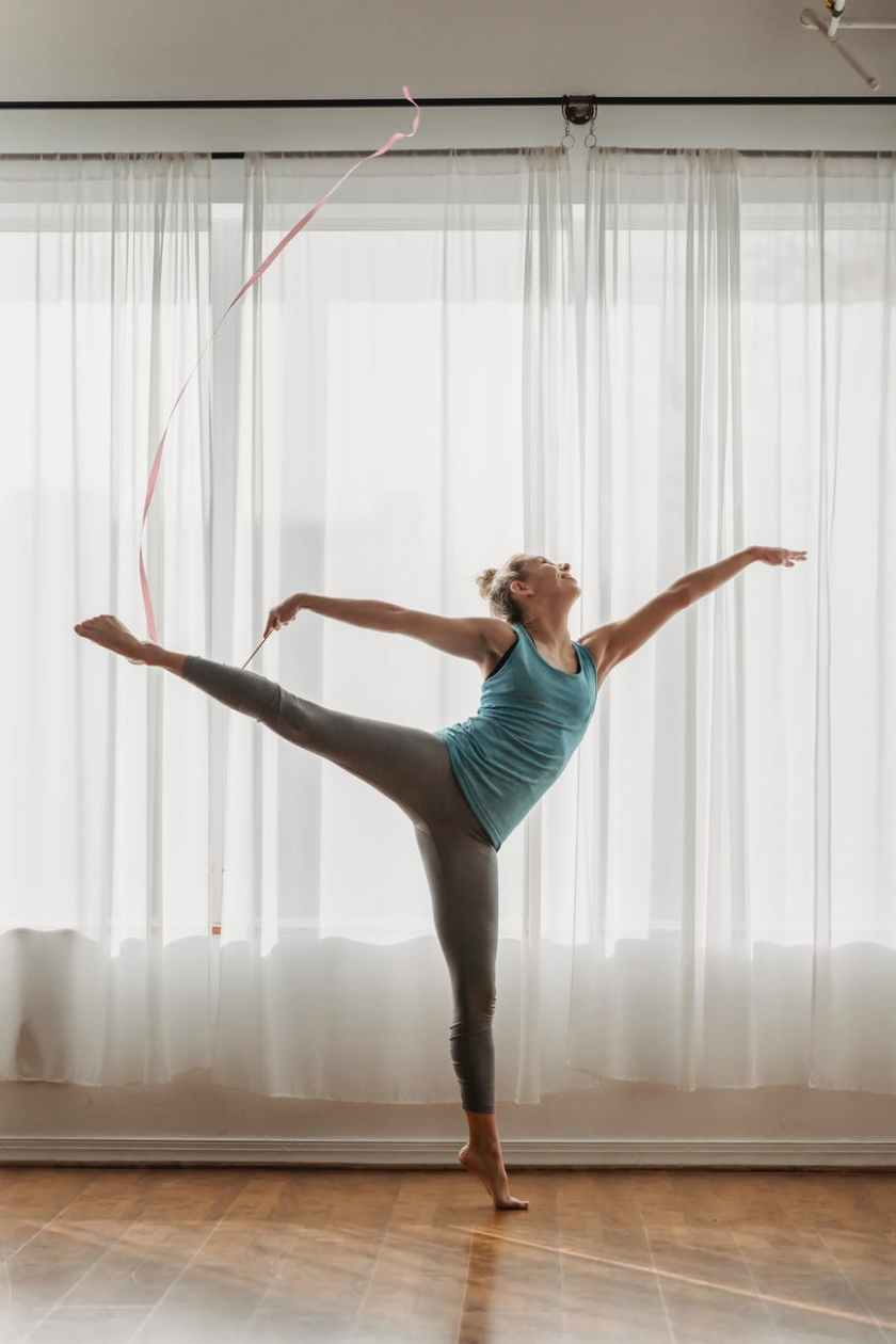 slender barefooted female gymnast exercising with ribbon in studio