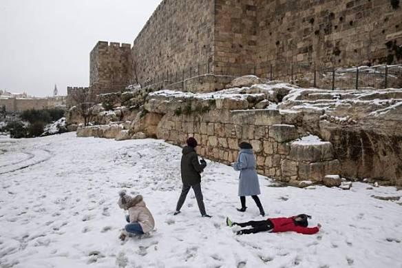 Orang-orang bermain di salju di taman di samping tembok Kota Tua Yerusalem, Kamis (18/2).