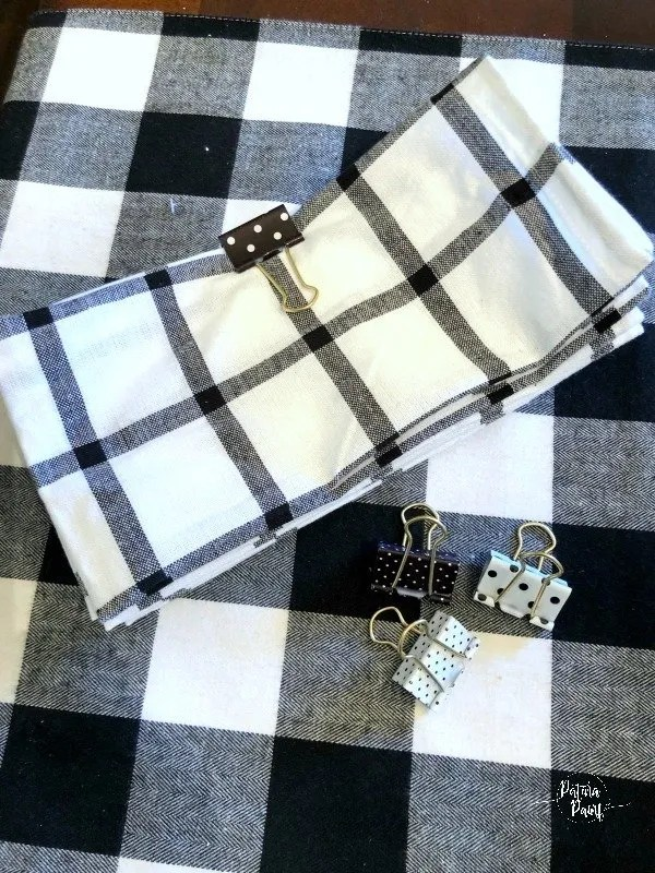 black and white napkins held by a binder clip