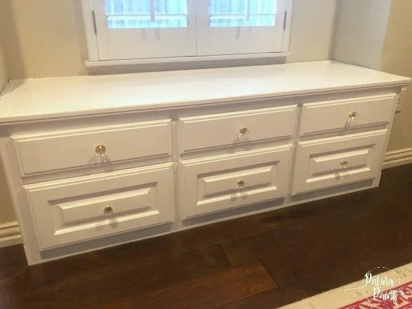 white window seat with drawers and glass pulls