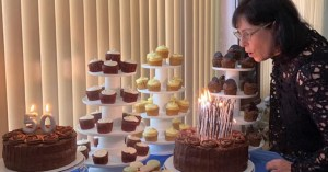 The Best Gift For My Milestone Birthday. Lisa-Michelle Kucharz blows out candles surrounded by cakes and cupcakes.
