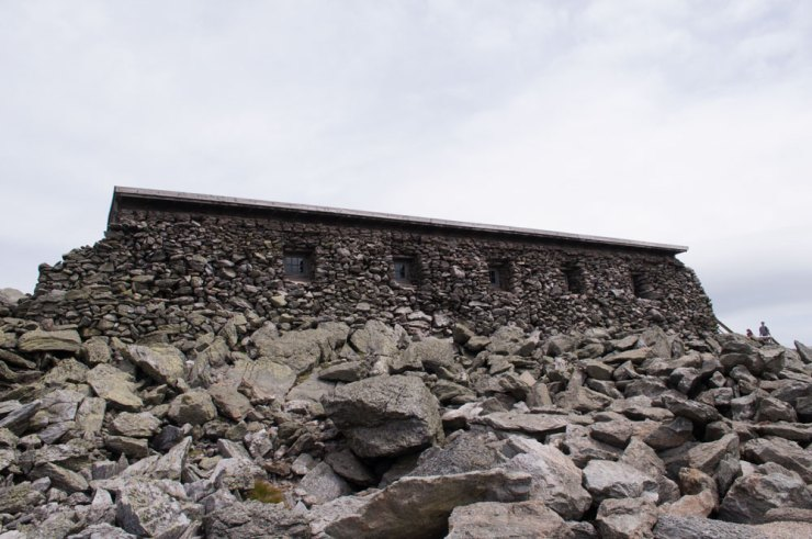 Cabin with thick wall covered in stones to survive the winter.