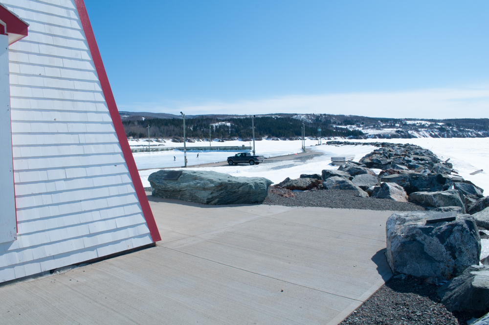 From the lighthouse, looking over the wharf where two people are seen skating on the ice.