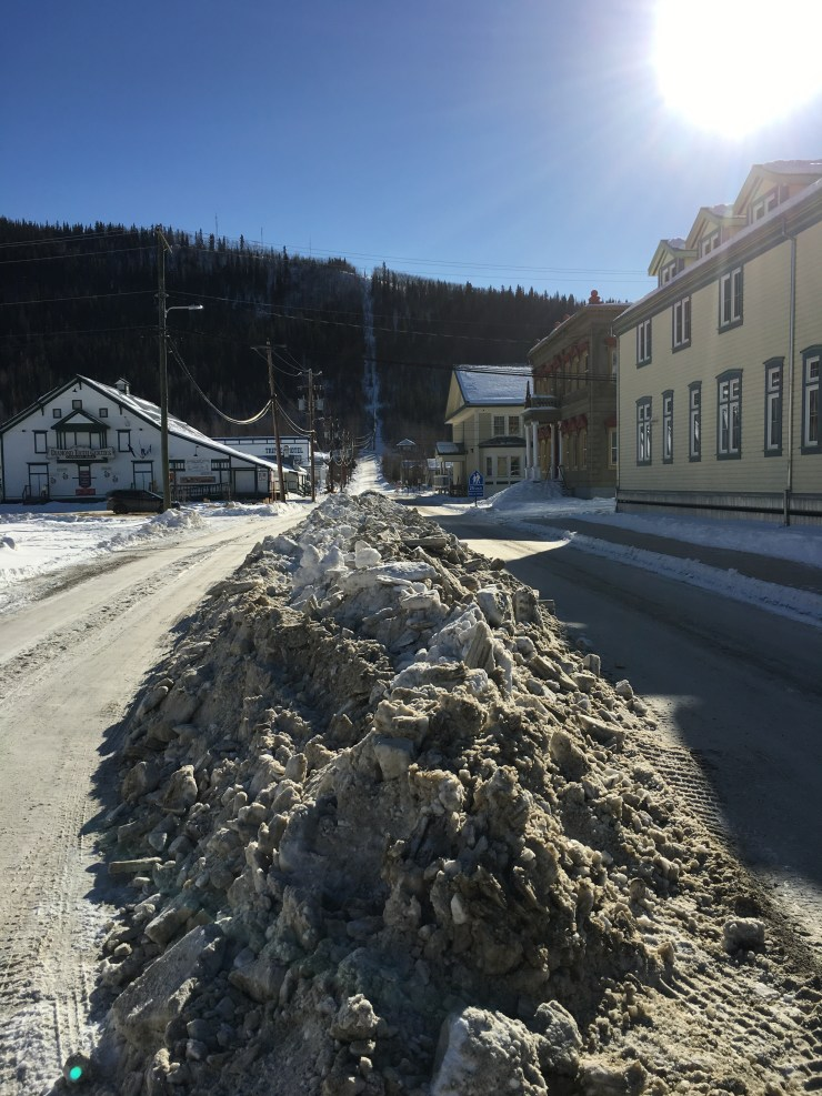 The town is working on grading the streets. They aren't plowed much in the winter, and now they are scraping them down to the frozen gravel.