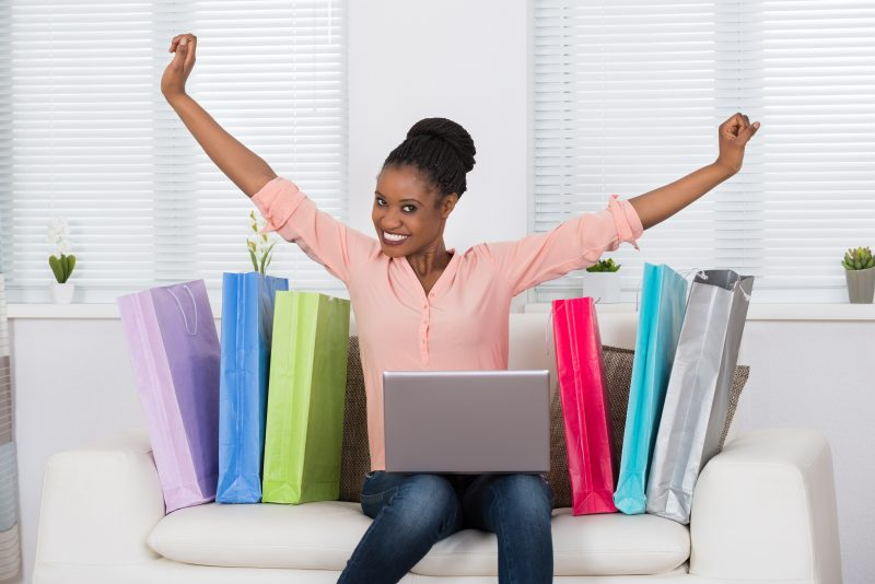 Young African Excited Woman While Shopping Online On Laptop
