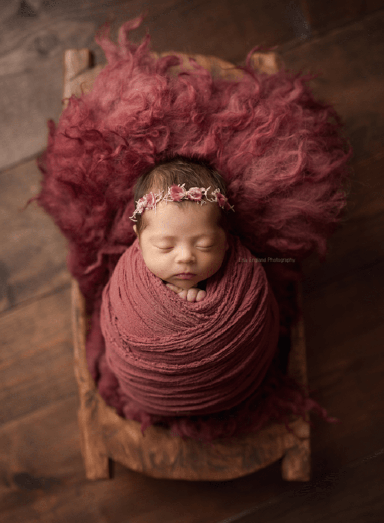 beautiful baby girl wrapped sleeping in a trencher bowl