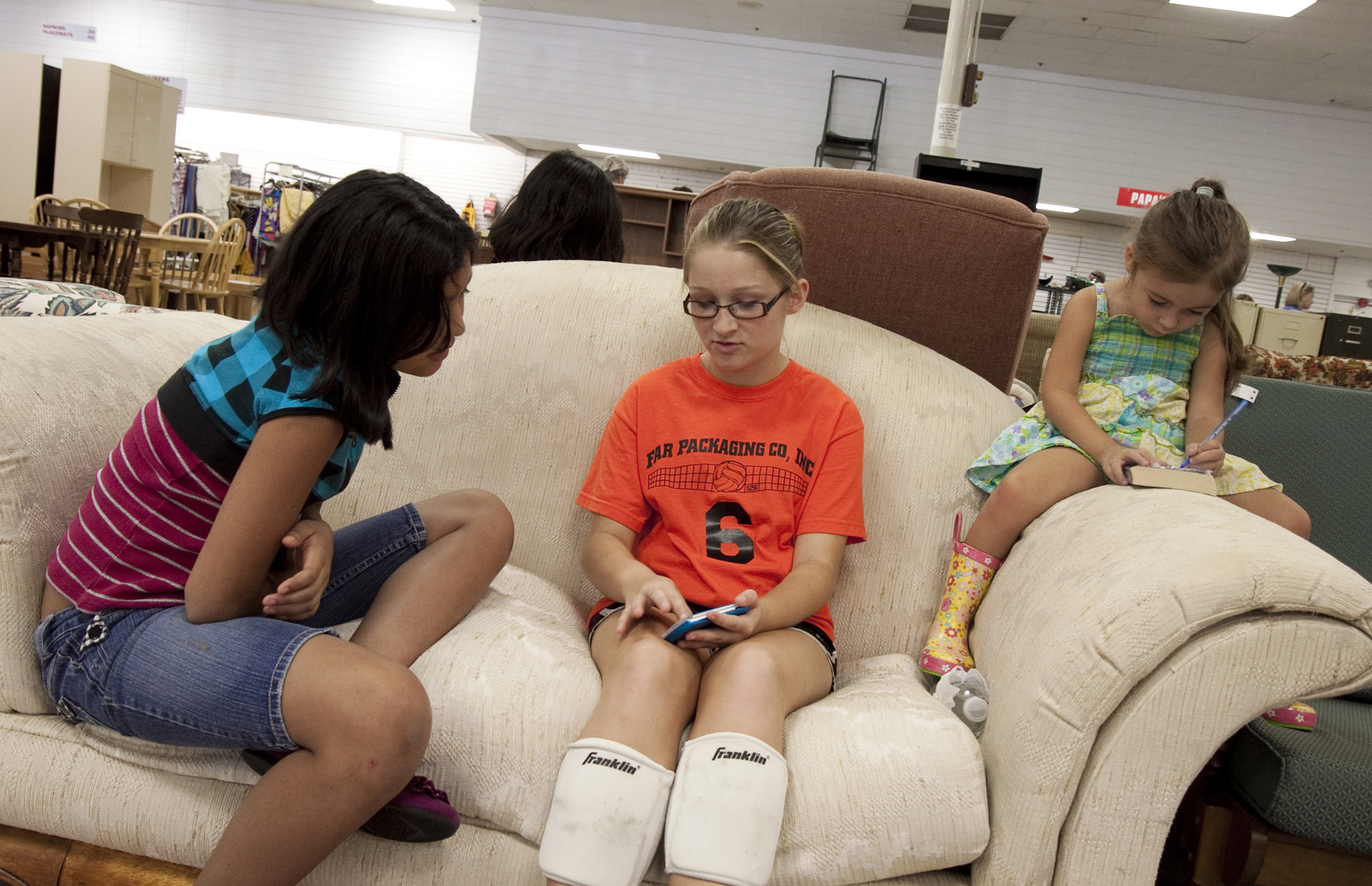 Yoisy Ordonez, 11, Alexis McLeod, 11, and Cira Smale, 4, wait for their parents to finish shopping in Guardian Angel Thrift Store, a reused Harris Teeter in Fuquay-Varina, N.C. Harris Teeter abandoned this location to move one mile up the road to a newer shopping center.