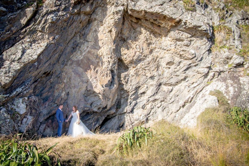Bride and Groom at cliff face on Pencarrow Coast