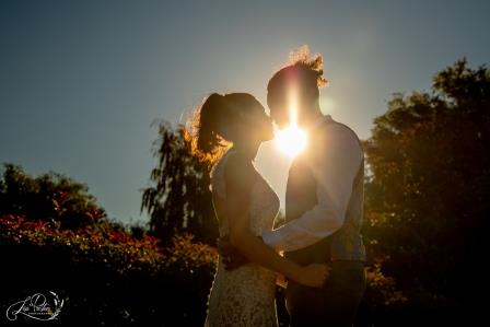 Bride and groom kissing at sunset, Lismore House