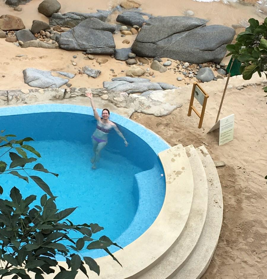 Lisa in a resort pool, waving