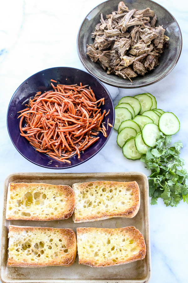 Tender steak and a tangy sauce along with easy pickled carrots make these banh mi inspired slow cooker steak sandwiches something special. | lisasdinnertimedish.com