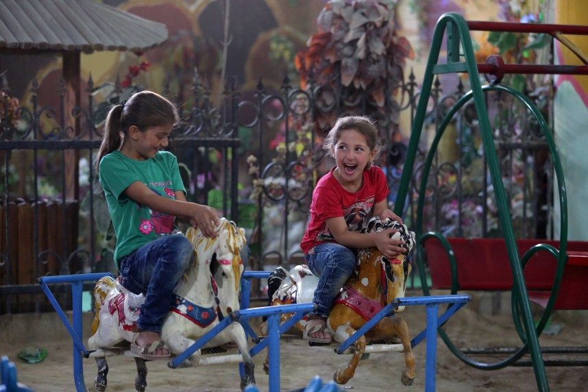 "On 17 September 2016, two girls play at the 'Land of Childhood' underground playground in a besieged town in in the Syrian Arab Republic. ""My friends and I come here because it's the last theme park that is still working [...] the one we used to go to was attacked and is not working anymore,"" one of the children said. A group of volunteers, led by a fourth-year former architecture student, links two basements with a tunnel and turns them into an underground playground to provide children with a relatively safe place to play and have fun together."