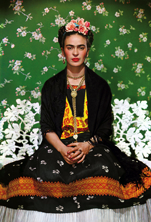 Frida Kahlo sits on a white bench, wearing traditional Mexican clothing, in her heavily ornamented and embroidered signature look. Photographed in 1939 in New York by her friend and lover, Nickolas Muray.