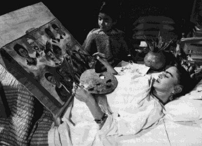 Frida Kahlo paints in bed.