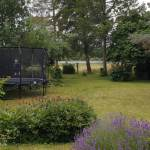 Udsigt til sigerslev mose. Dreng hopper i trampolin i haven.