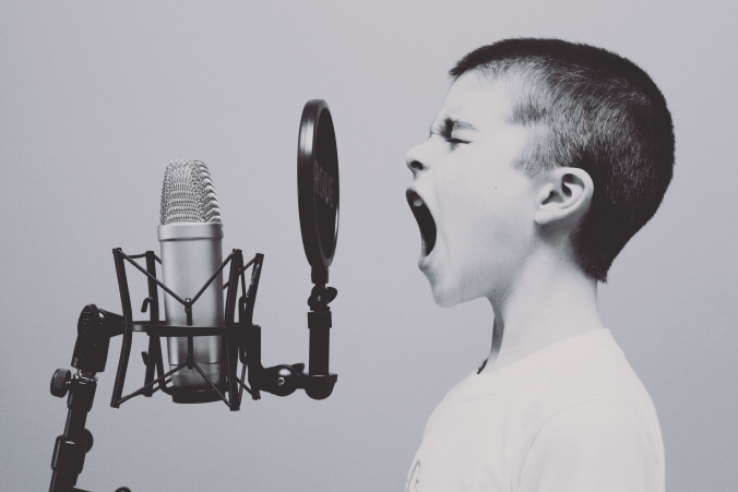 image of a child at an old fashioned microphone with mouth open wide for article on why you need a theme song today