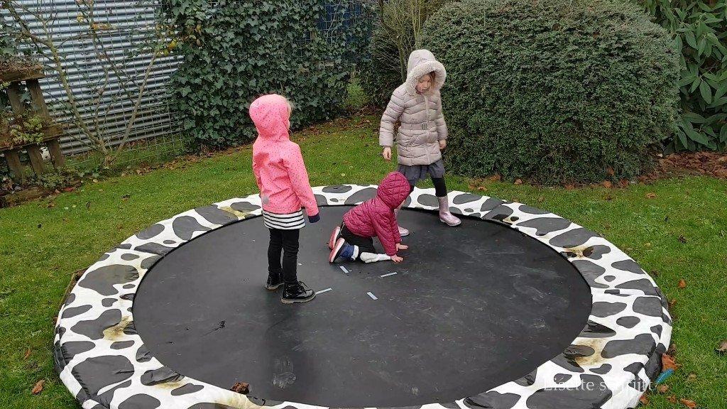 kinderen spelen op een trampoline in de regen