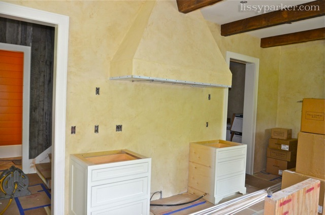 The range hood and walls are beautiful plaster—great warm color and beams