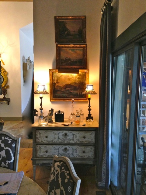 Small painted chest, small lamps and three landscapes are opposite the table