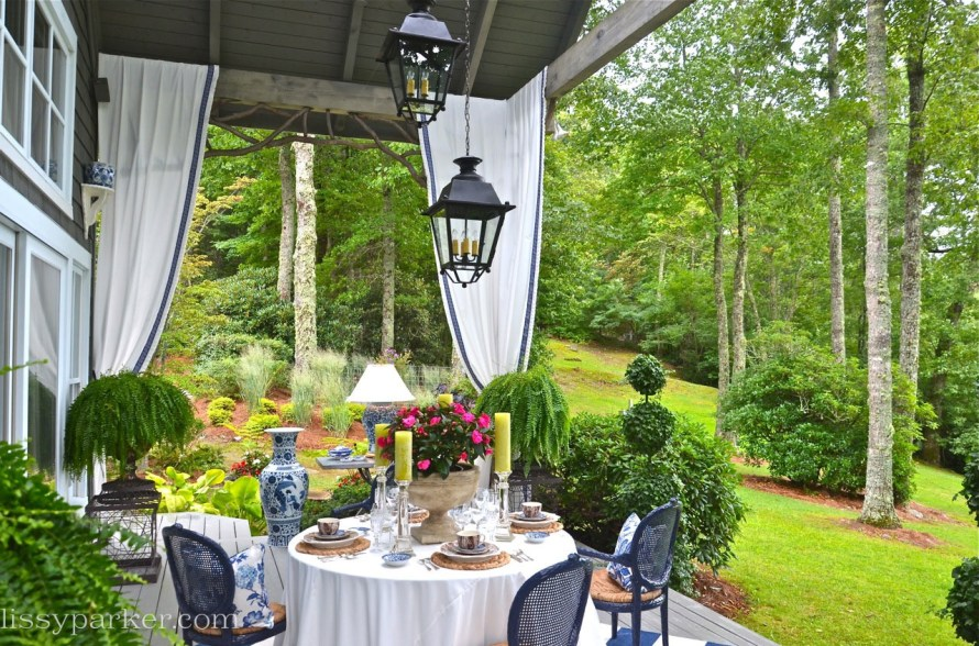 Large Urns lined with moss and filled with ferns anchor the corners of the porch—topiary frame the stairs