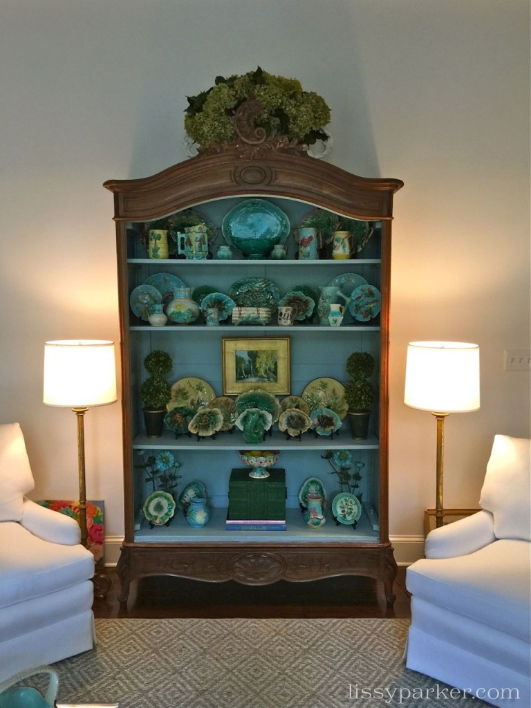 A large majolica collection pops in this painted antique cabinet.