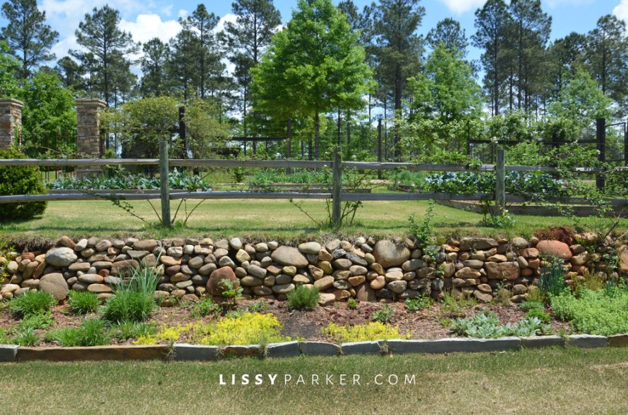 The whole garden is raised and surrounded by a stone wall and fence