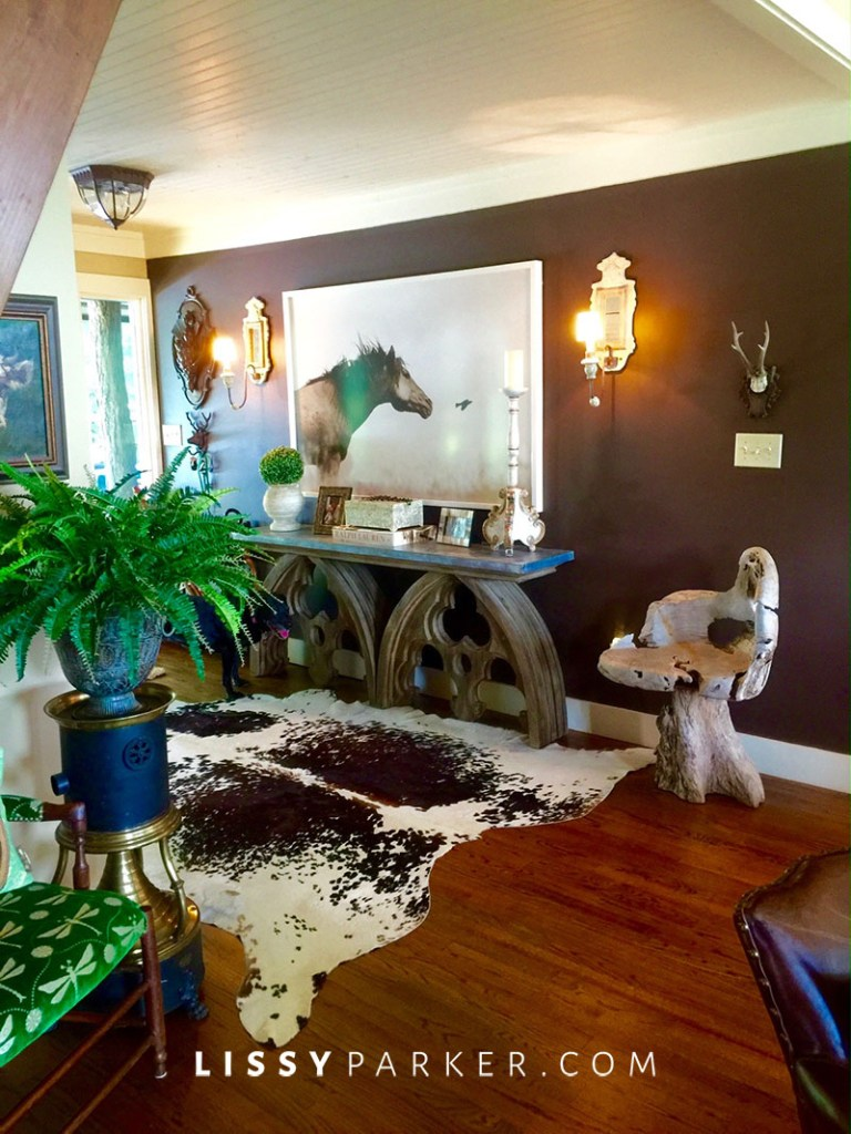 brown walls and a horse painting in the entry