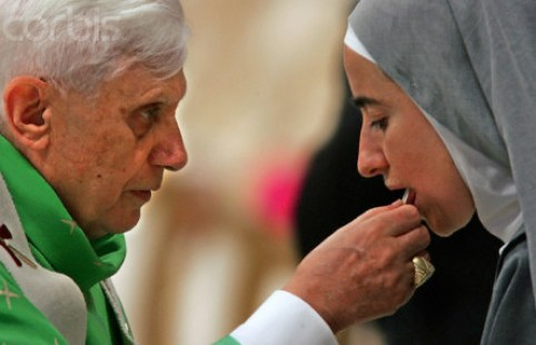 """02 Oct 2005, VATICAN CITY, Vatican --- Pope Benedict XVI gives the communion to a nun during a solemn mass in Saint Peter's Basilica at the Vatican for the opening of the synod of the bishops October 2, 2005. Pope Benedict opening the first major Church meeting since his election, said on Sunday that trying to keep God out of public life was """"not tolerance but hypocrisy."""" The Pope also said that too many Catholic lives could be compared to """"vinegar rather than wine"""" because of the indifference to God. --- Image by © MAX ROSSI/Reuters/Corbis"""