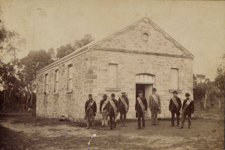 Members of the Meadows Lodge of the Oddfellows, standing outside the Lodge building, date unknown.