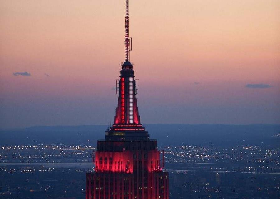 Empire State se ilumina rojo y blanco para honrar combatientes COVID-19