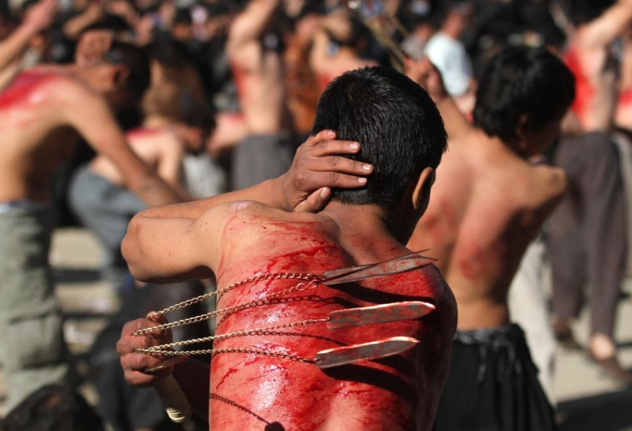 199920-Shia-Muslims-Flagellate-Themselves-Walk-On-Fire-Prior-To-Ashura