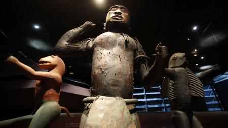Three large royal statues of the Kingdom of Dahomey are displayed at the Quai Branly Museum in Paris, France