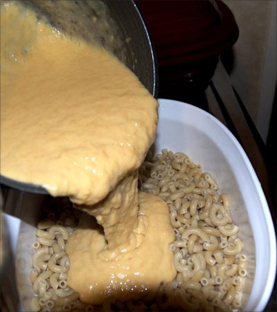 pouring Daiya over macaroni