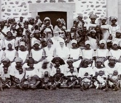 Women posing for a group photograph with their babies outside the Maternity Institute of Abeokuta, c.1929.