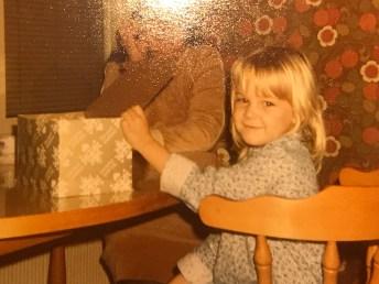 I fyra-femårsåldern. Med tidstypiska tapeter och möbler och ett paket. Men troligen en födelsedagspresent snarare än en julklapp.