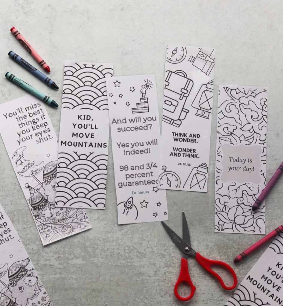 Top down of the five printed bookmarks on a marble board with crayons and scissors.