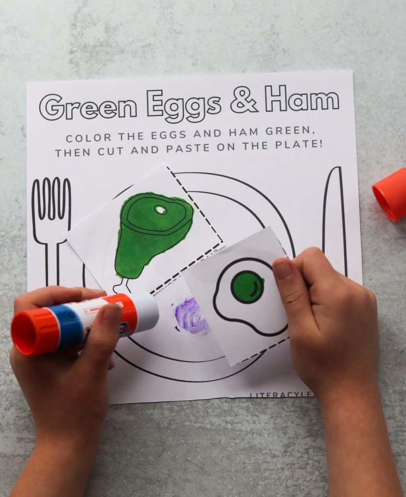 A child's hands glueing the cut pieces of the green eggs and ham activity page together.