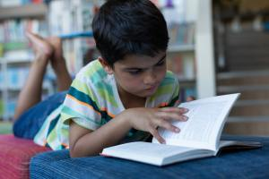 Concentrated schoolboy reading a book while lying on sofa in library at school