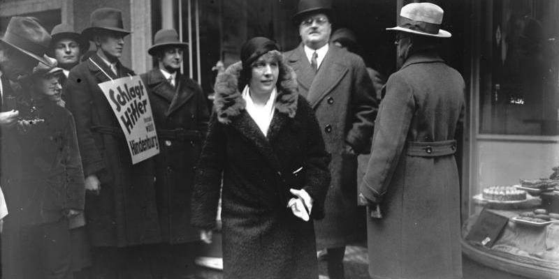 """1932 год. Отто Мейснер выходит из конторы. У немцев рядом плакат с надписью """"Долой Гитлера! Голосуйте за Гинденбурга!"""""""
